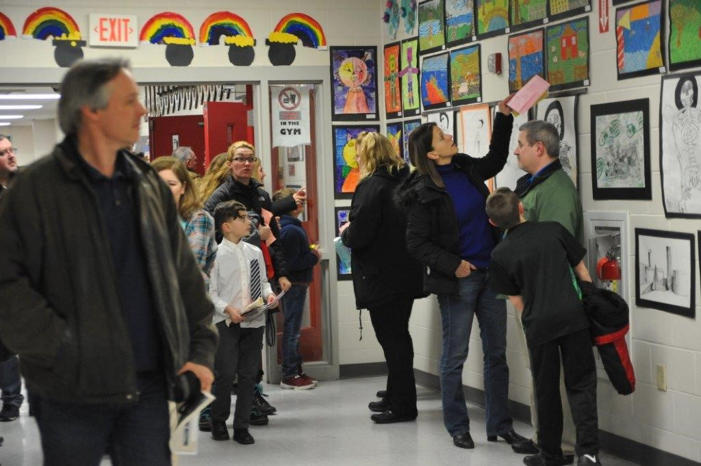 Parents and Community Members Admire Student Art.