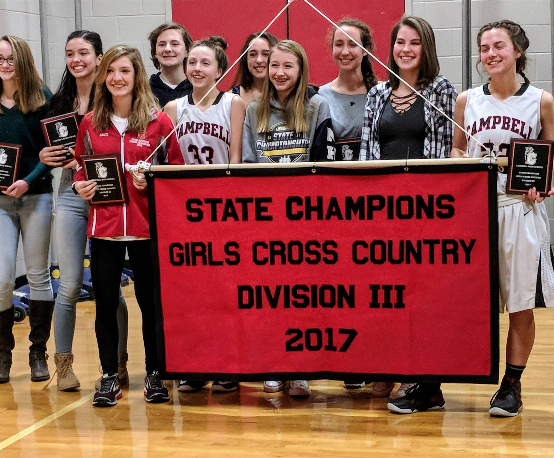 Raising the Girls Cross Country 2017 State Champion banner